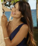 female model wearing a gold Hawaiian jewelry bracelet, ring and pendant by Maui Divers Jewelry