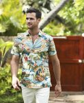 male model wearing a light blue aloha print shirt with palm tree and hula girl imagery