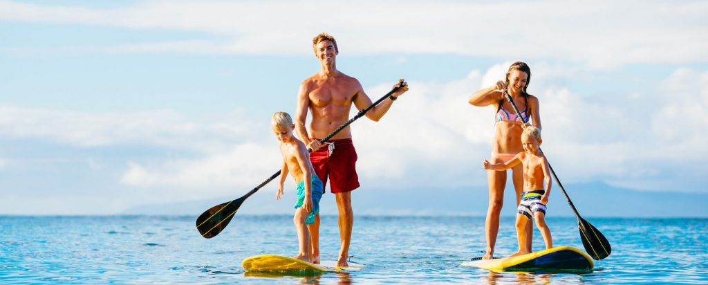 family enjoying a stand up paddling session in the ocean